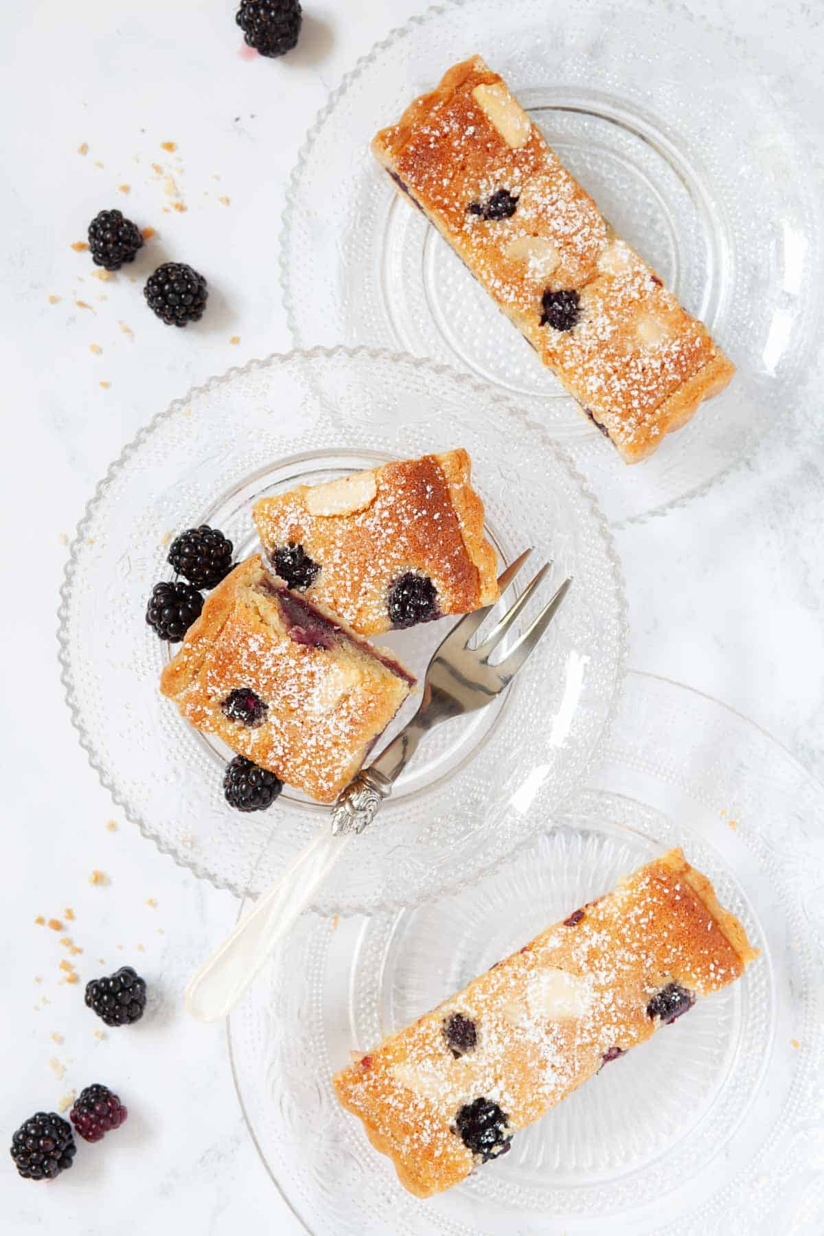 Slices of almond frangipane tart with blackberries on glass plates