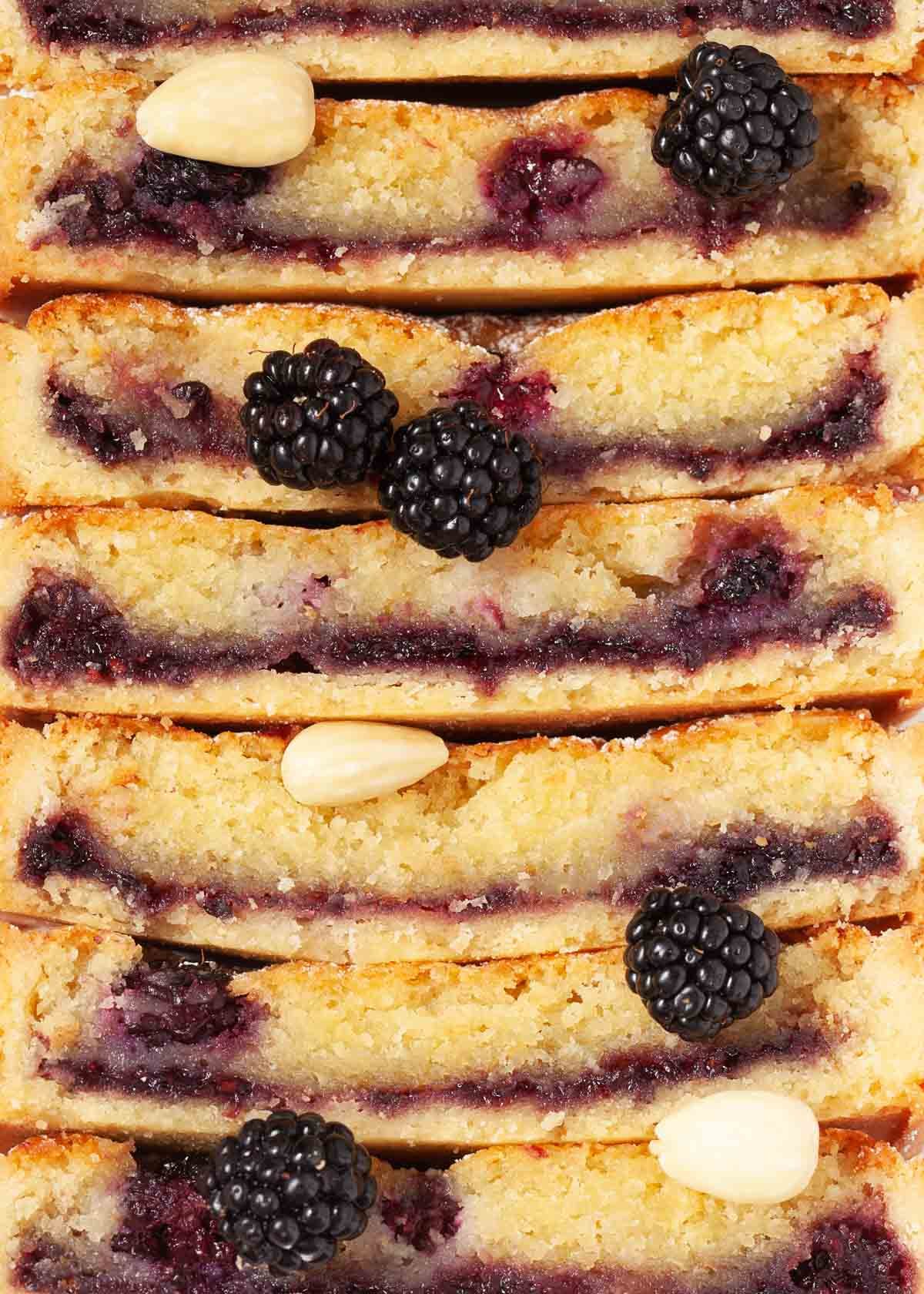 Close up of stacked up almond frangipane tart slices with blackberries