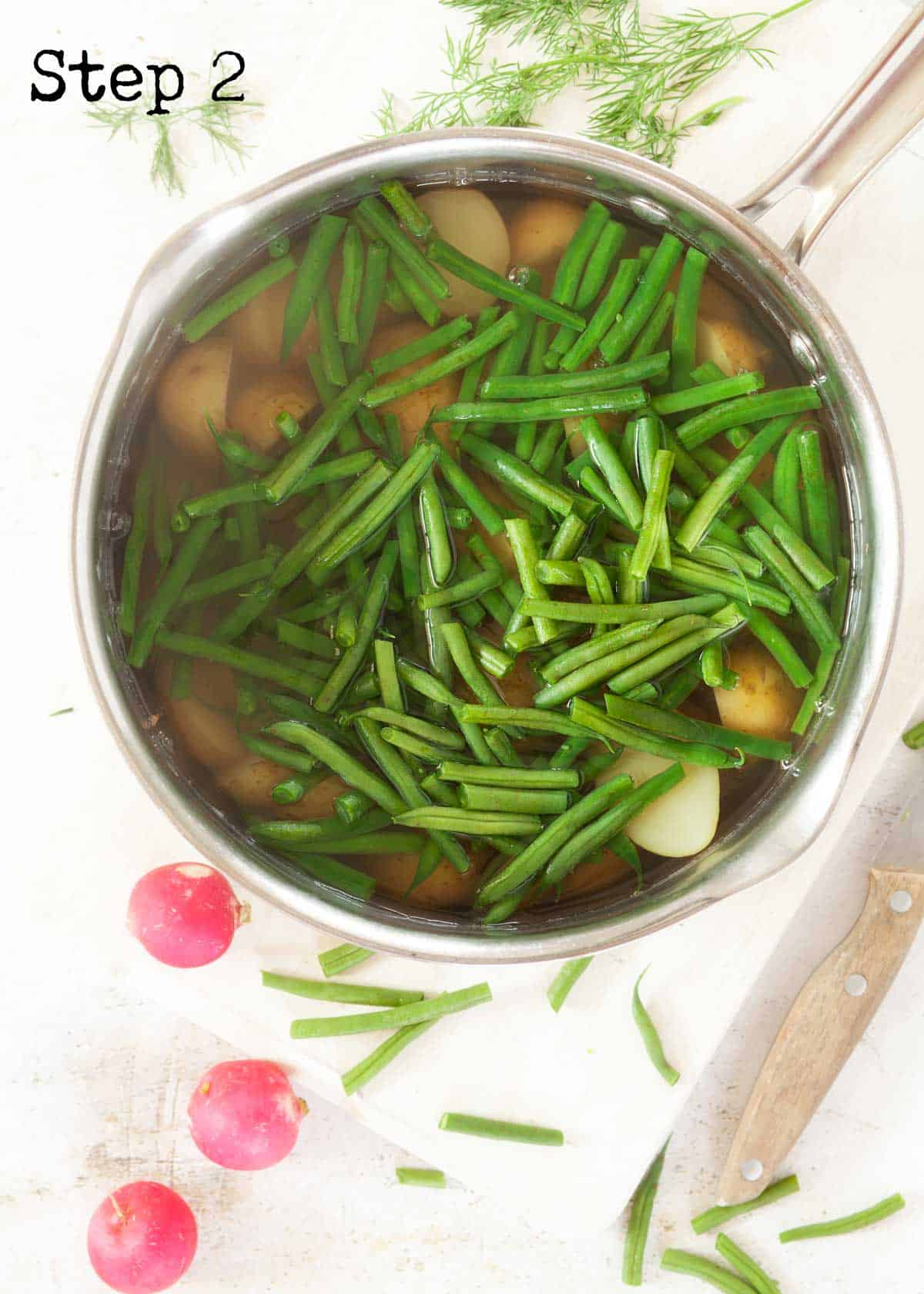 Process image - green beans added to a pan of cooked potatoes