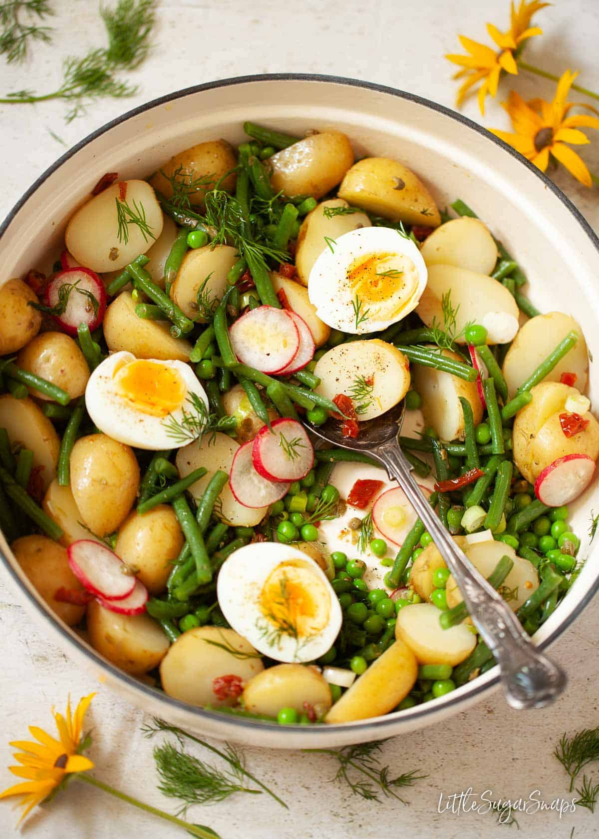 A pot of green bean and potato salad topped with hard boiled eggs
