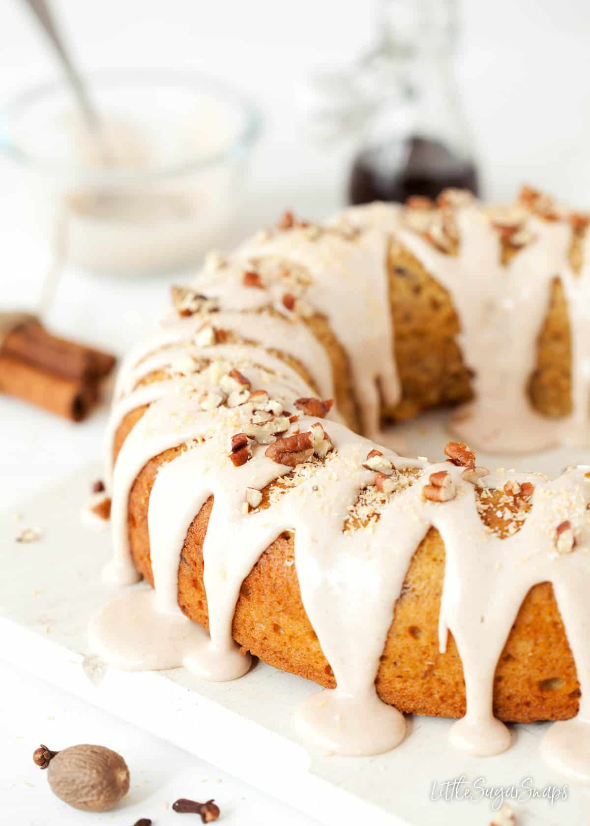 Close up of a pumpkin spice bundt cake with maple icing, toasted coconut and pecan nuts.