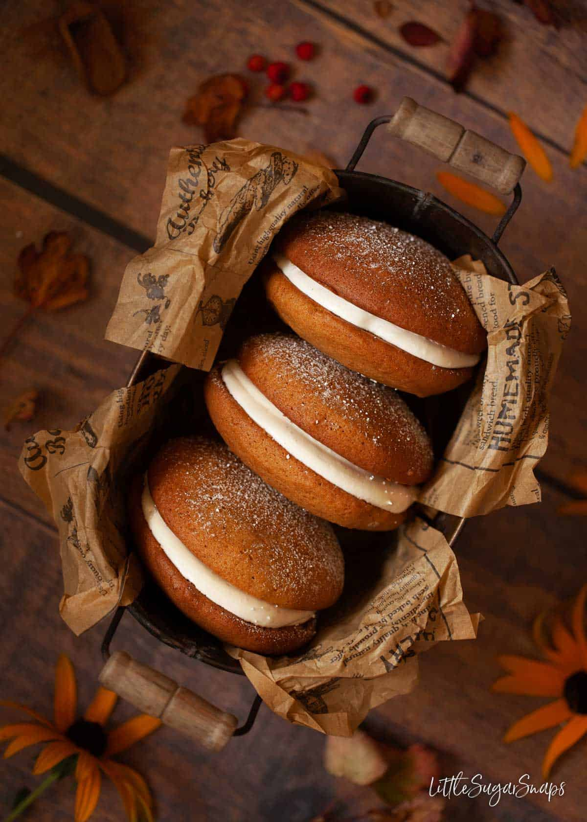 Overhead view of three pumpkin whoopie pies in a tin