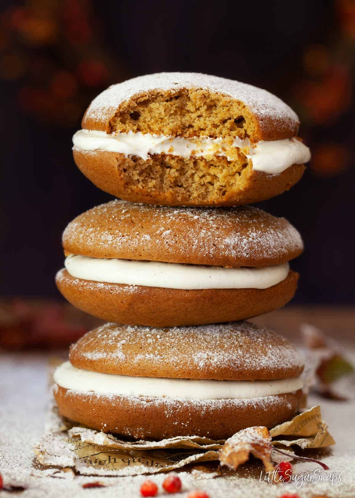 A stack of pumpkin whoopie pies. One has been bitten into.