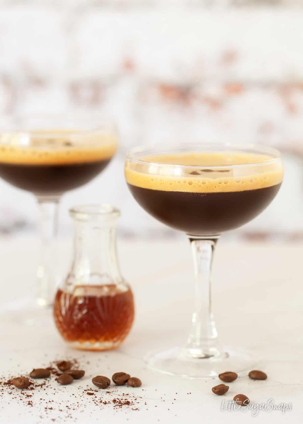 Glasses of caffè shakerato with a bottle of demerara sugar syrup