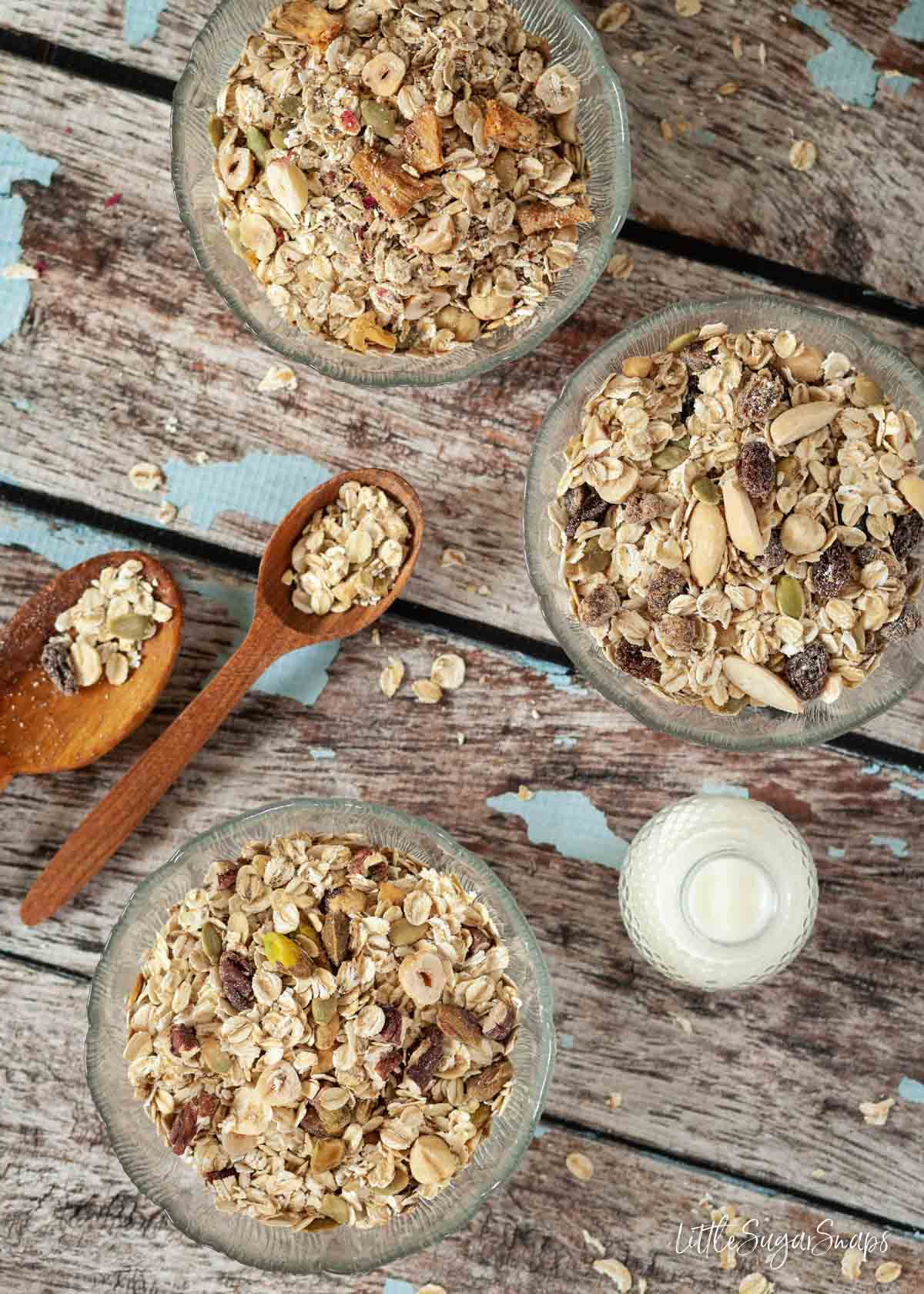Three bowls of oats, nuts, seeds and dried fruits with a small bottle of milk