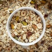 A bowl of muesli on a baking sheet with more muesli on it