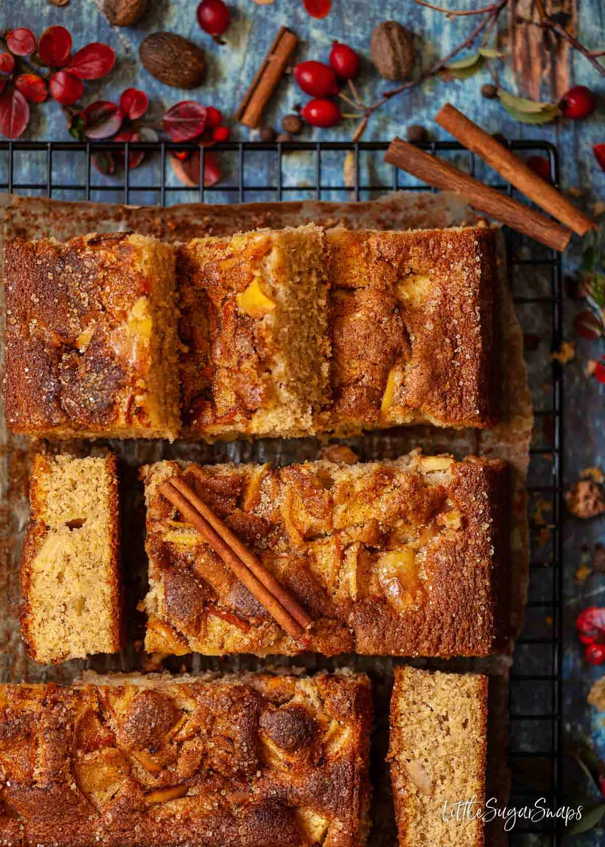 Pieces of traybake cake topped with apple on a wire rack with spices.
