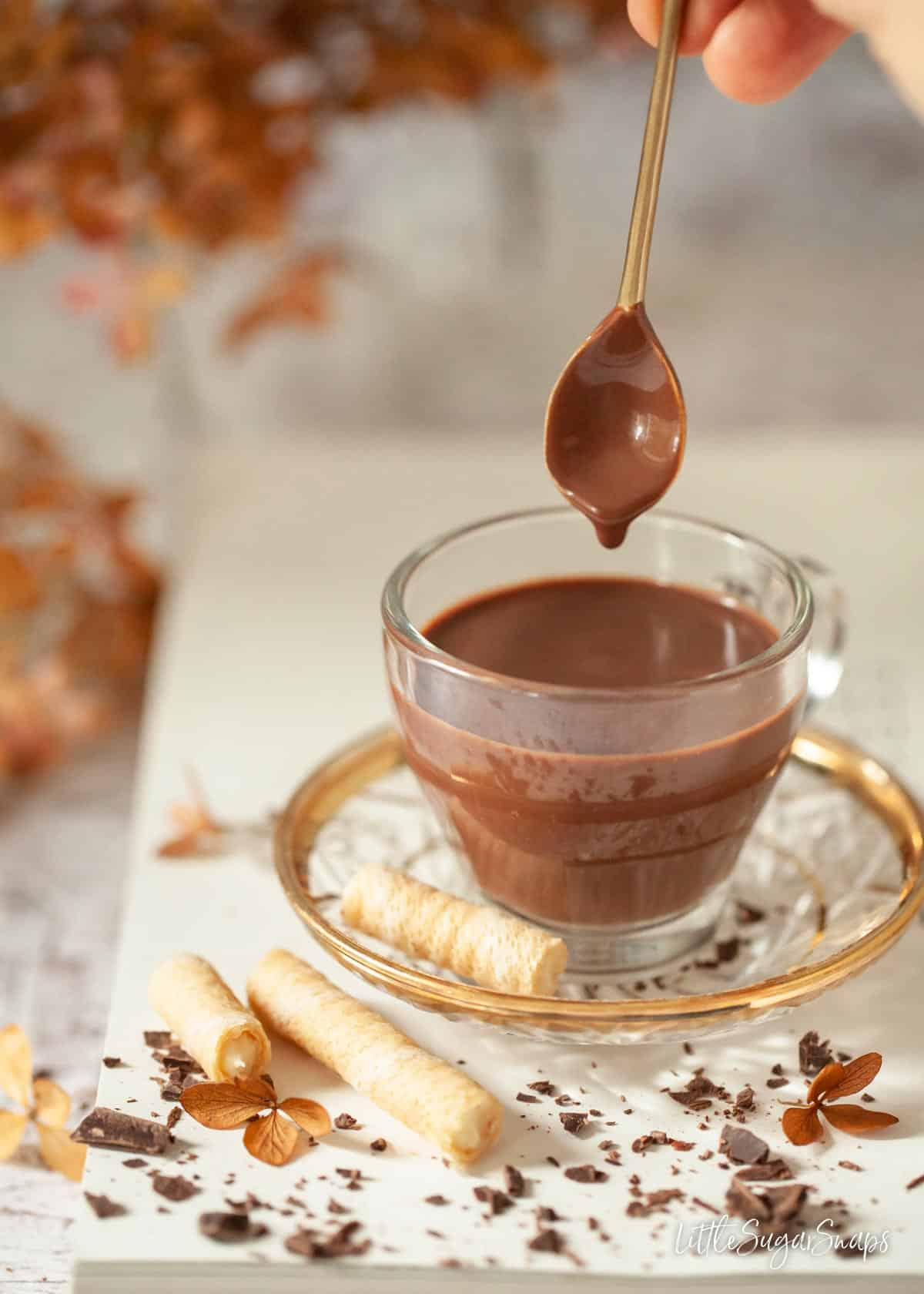 Thick Italian hot chocolate in a glass cup with a spoon being dipped in.