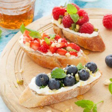 Mixed fruit breakfast bruschetta on a wooden platter
