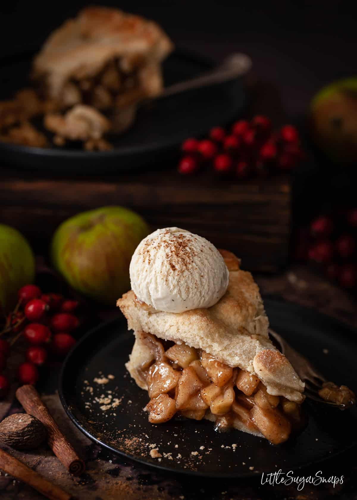 A slice of vegan apple pie with dairy free ice cream on top