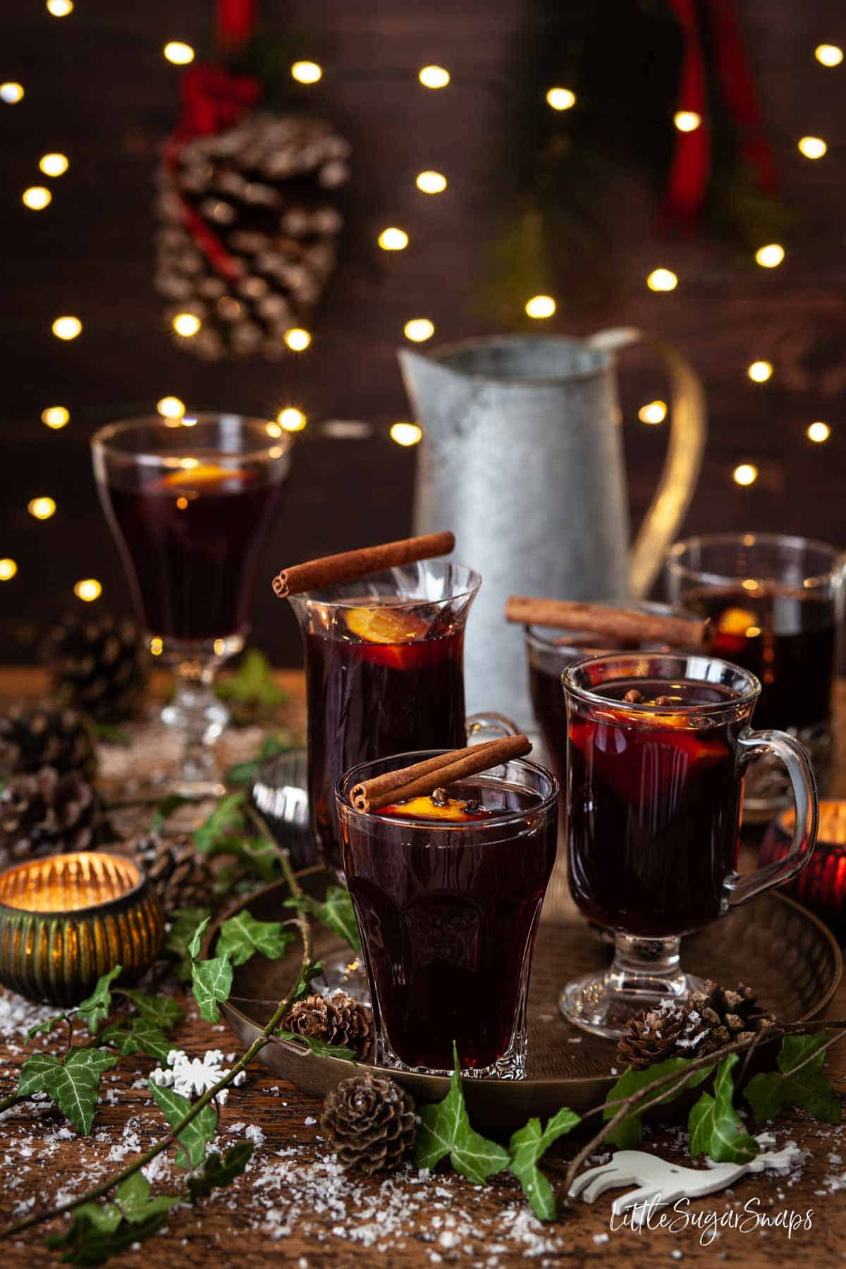 Glasses of vin brulé topped with cinnamon sticks and orange slices