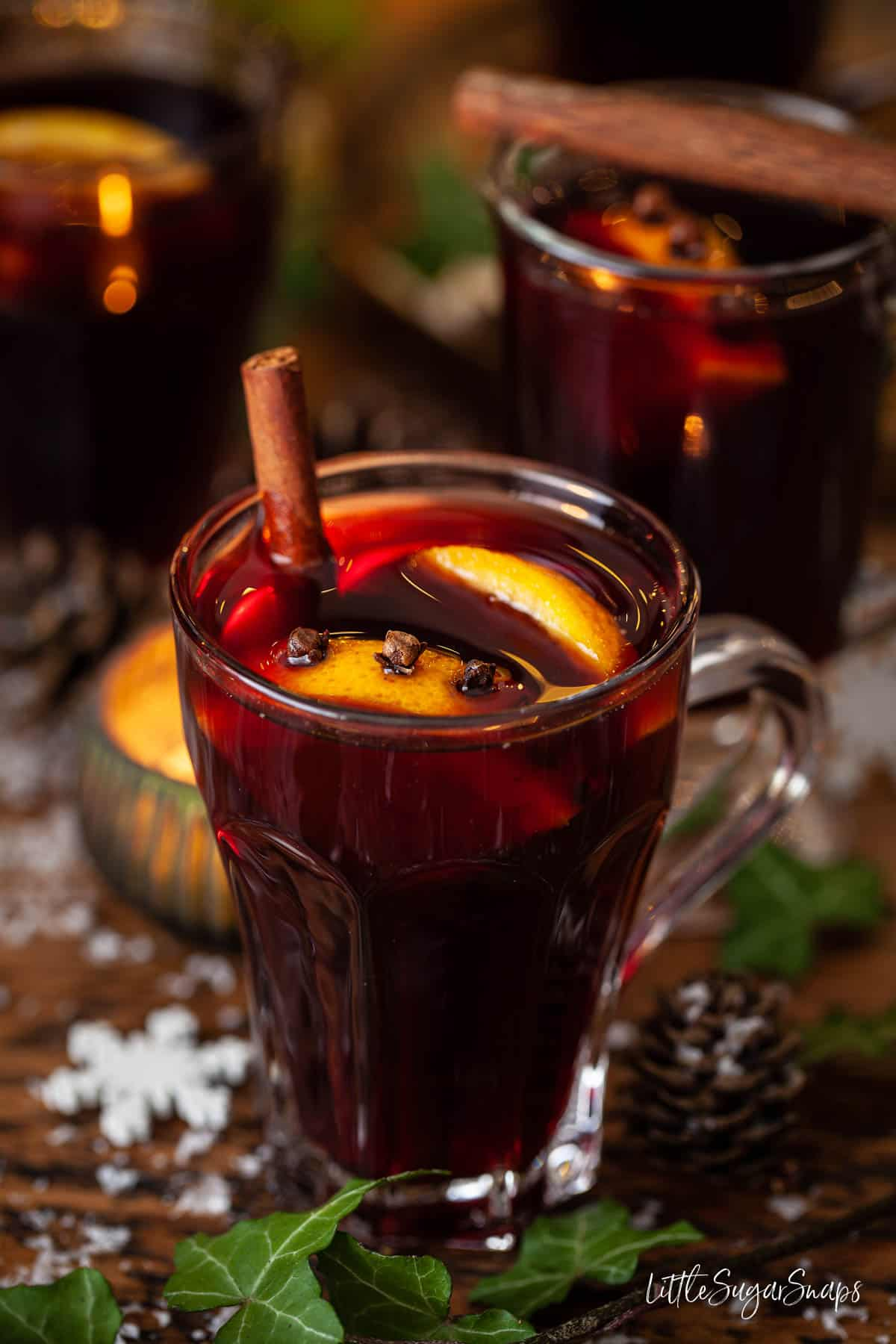 A glass of mulled wine with cinnamon, orange slices and cloves