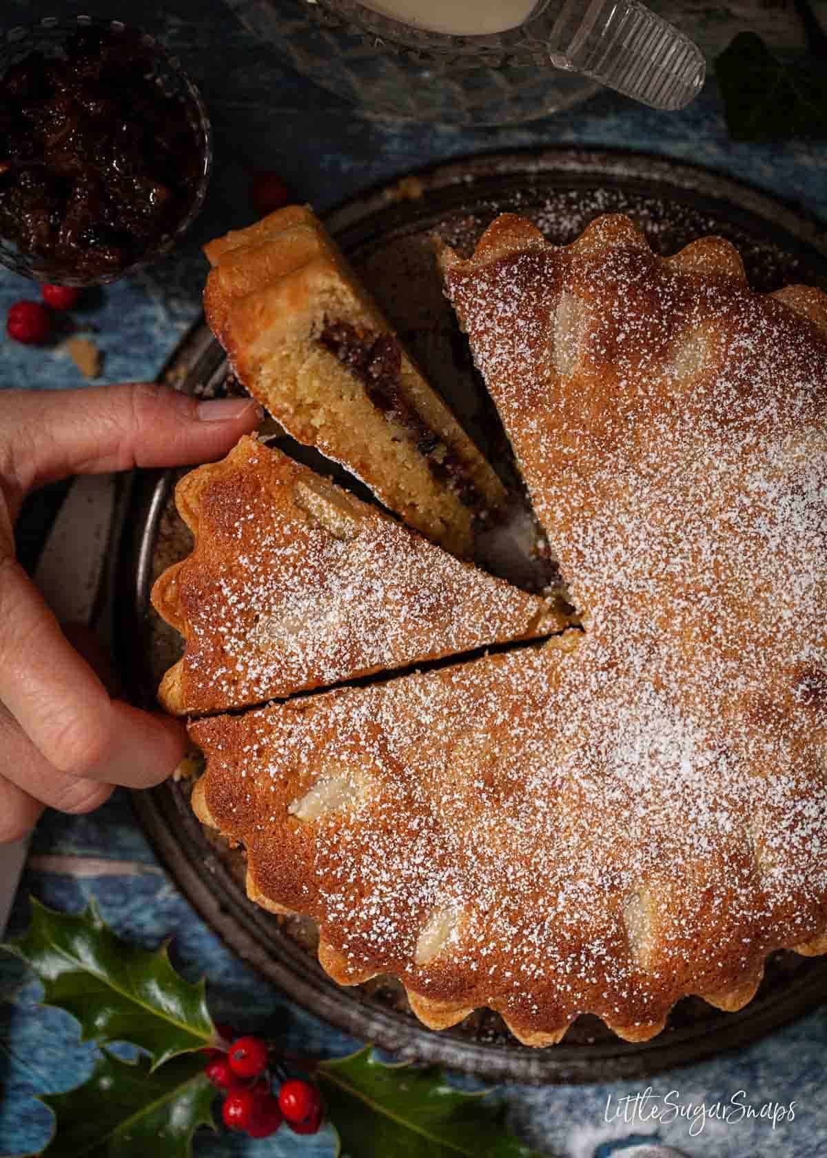 Person taking a slice of frangipane mince pie tart filled with mincemeat