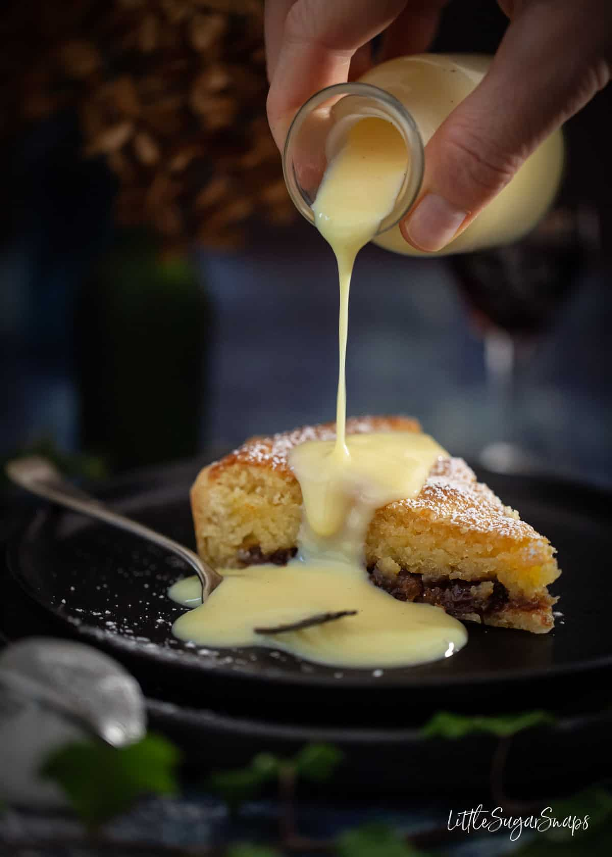 Person pouring custard over a slice of mincemeat tart with frangipane