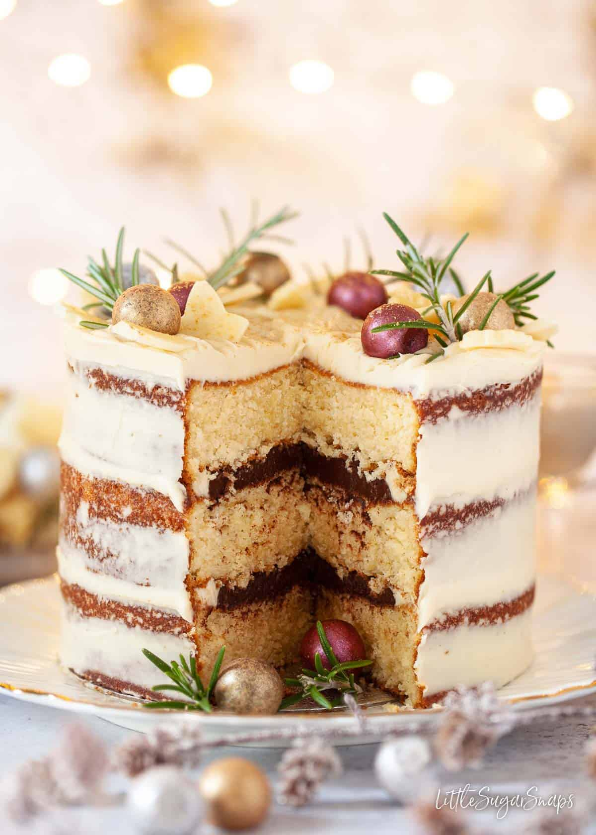A festive white chocolate cake with a slice cut out of it