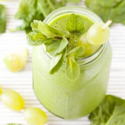 A green grape smoothie topped with fruit and mint