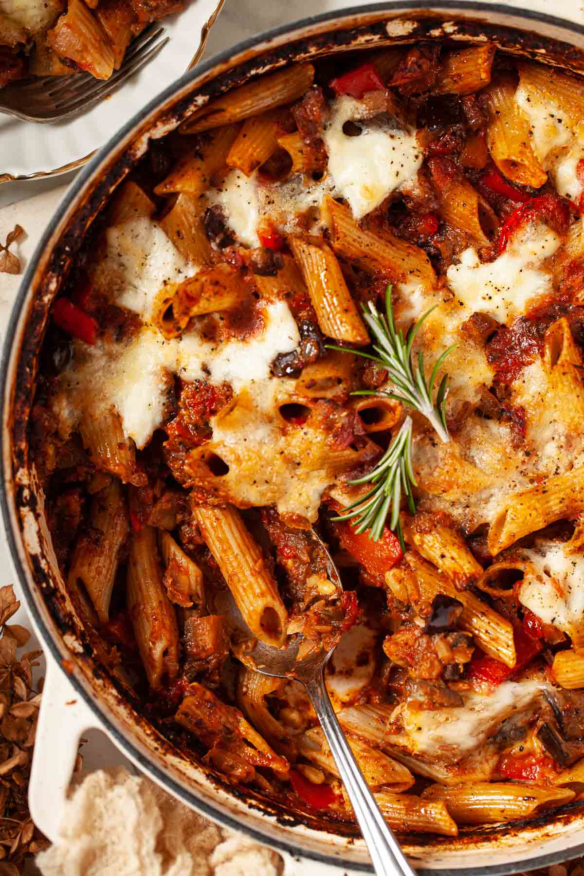 Close up of pasta al forno in a large serving pot with a spoon in it