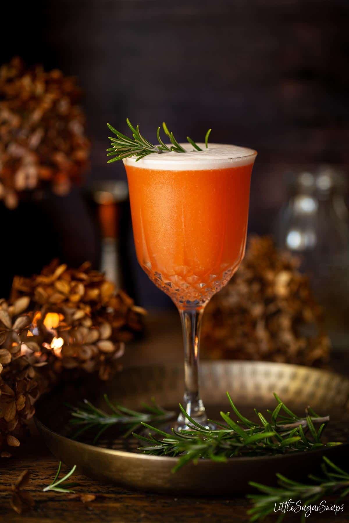 Straight on photo of Aperol sour gin cocktail with rosemary garnish