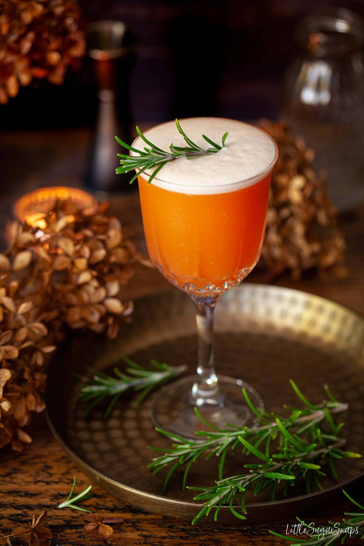 Aperol sour cocktail with egg foam and rosemary garnish