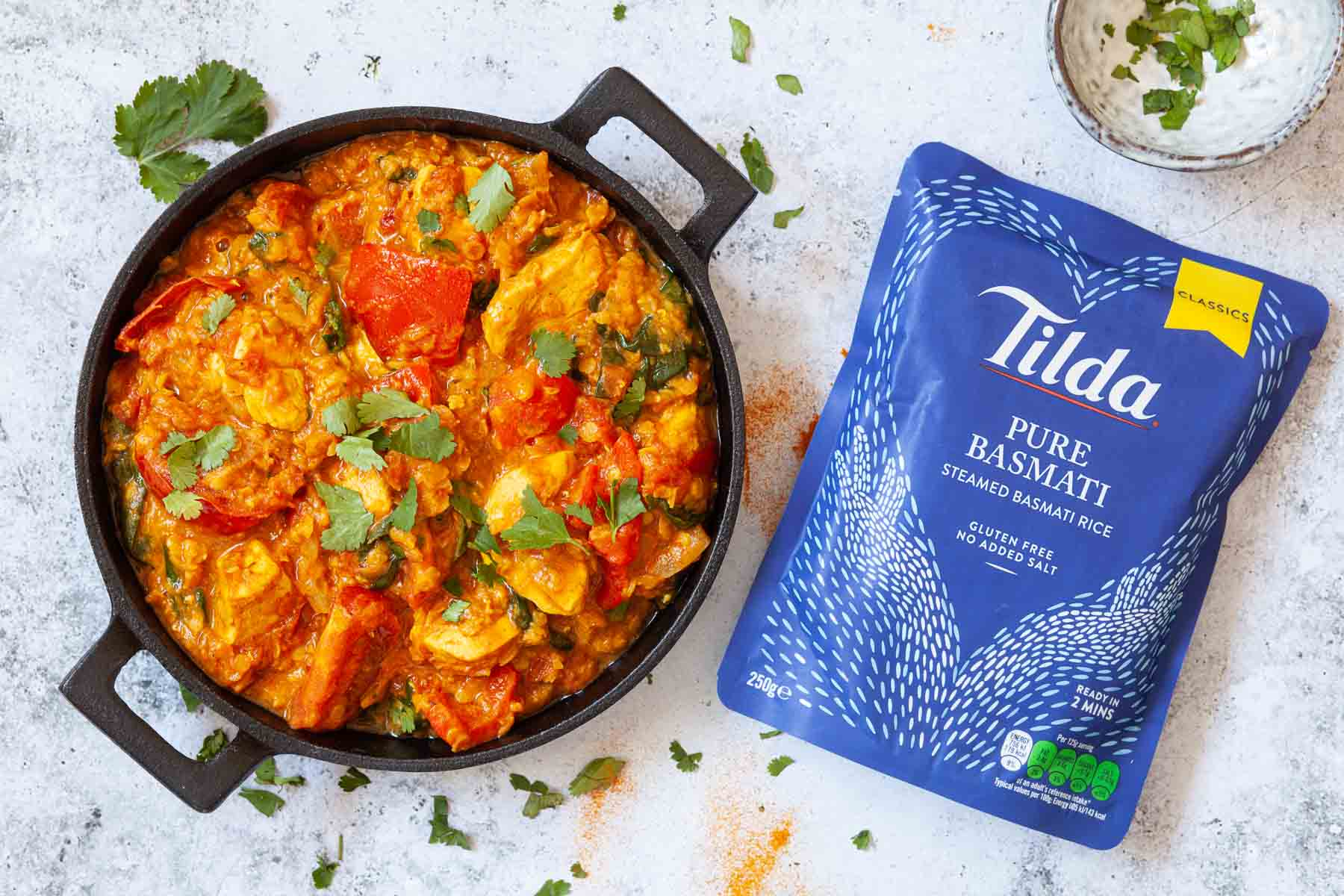 A skillet of chicken and lentil curry with a packet of microwaveable rice