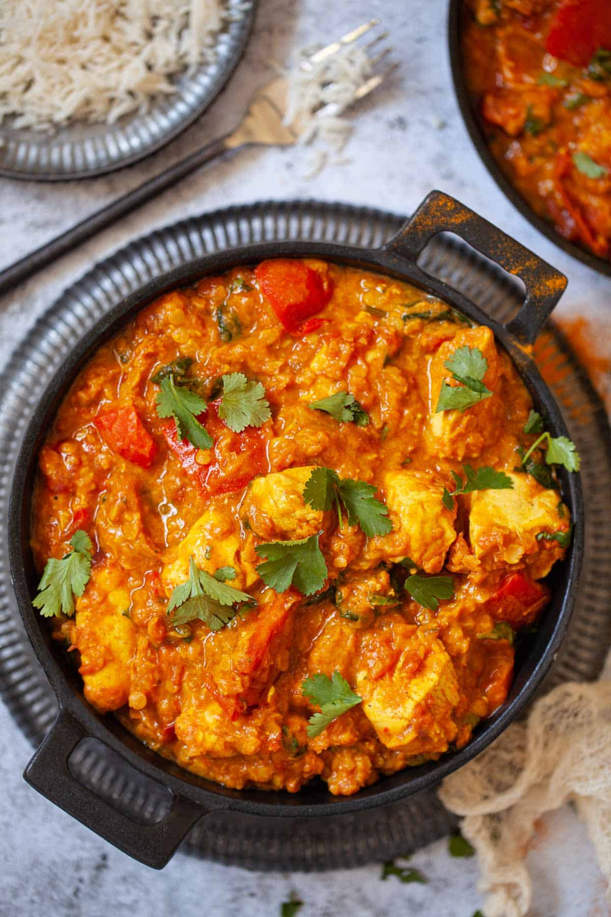 A skillet full of chicken lentil curry