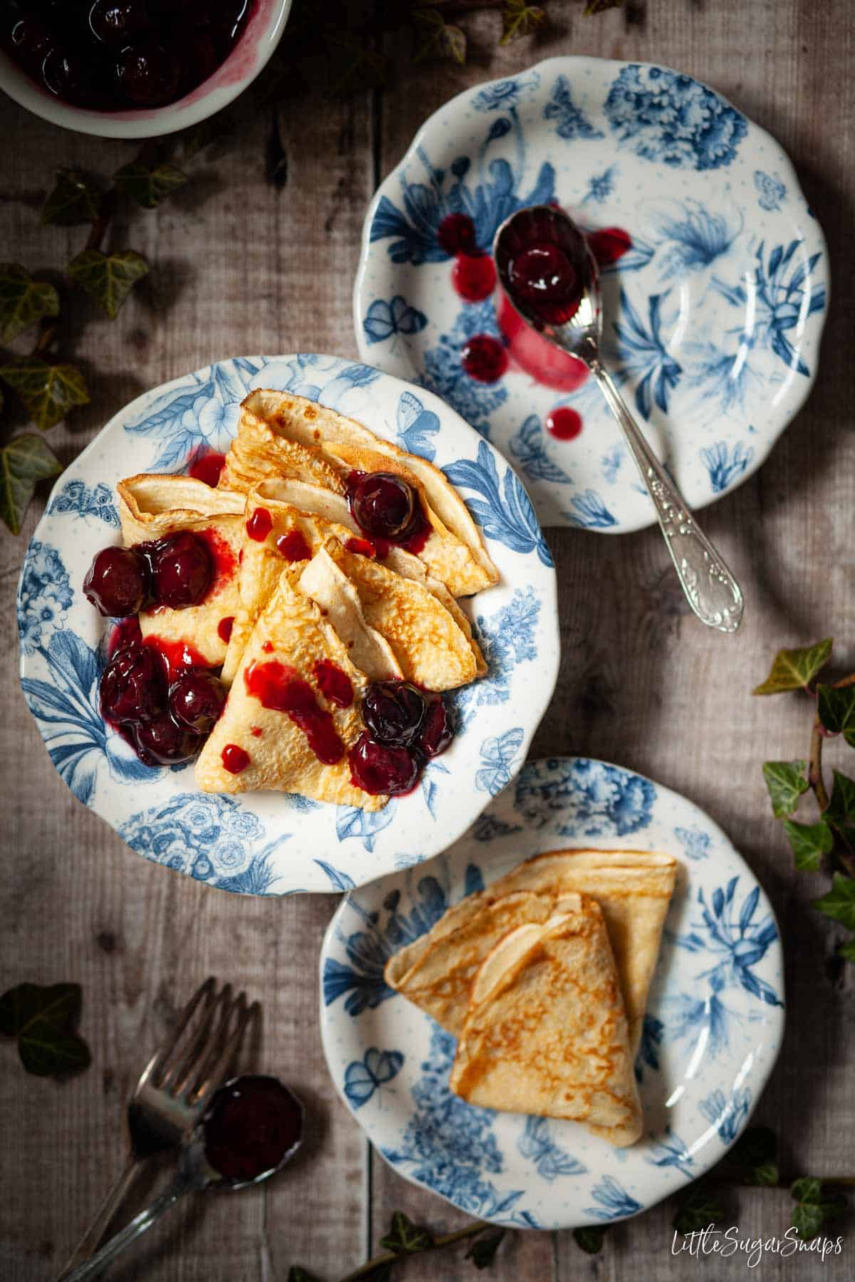 A plate of English thin pancakes with cherry sauce drizzled on top