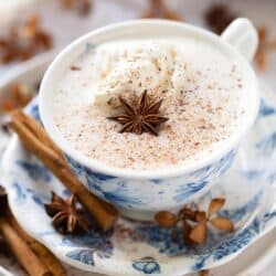 A cup of spiced hot chocolate with whipped cream, ground spice and star anise garnish