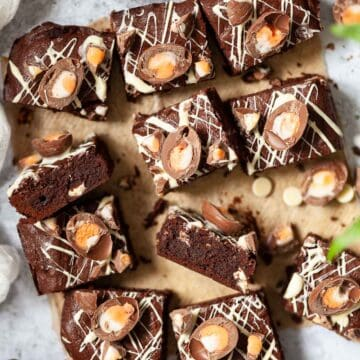 Squares of Easter themed brownies topped with chopped creme eggs