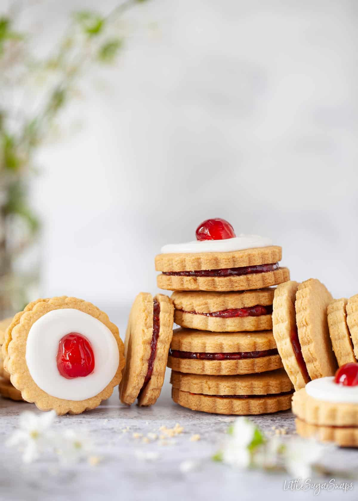 Empire biscuits stacked up. Some are iced and topped with cherries, some are not