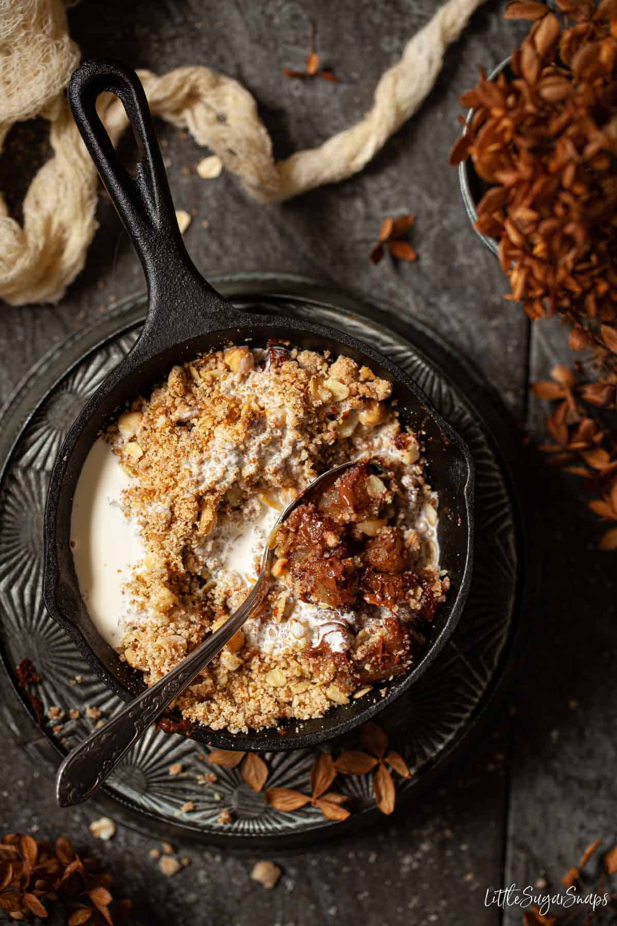 A single serve skillet of chocolate and pear crumble with pouring cream