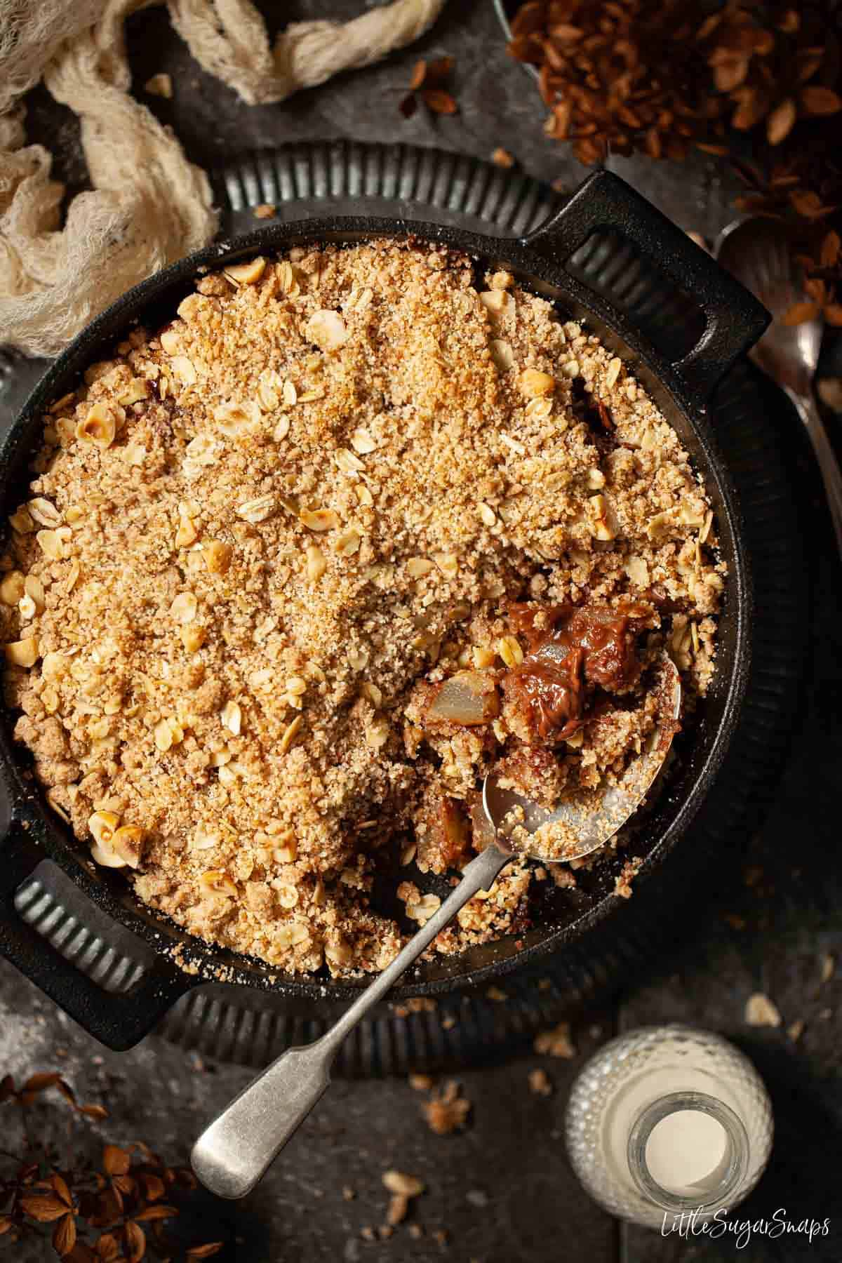 Chocolate and pear crumble in a cast iron skillet with a serving spoon in it