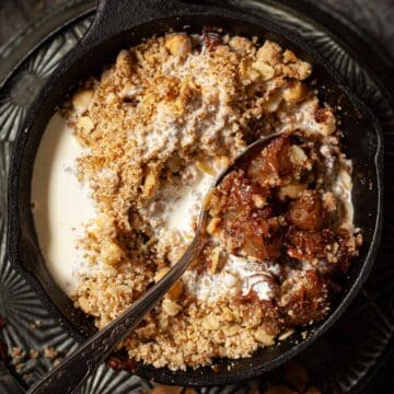 Pear crumble in a skillet with cream