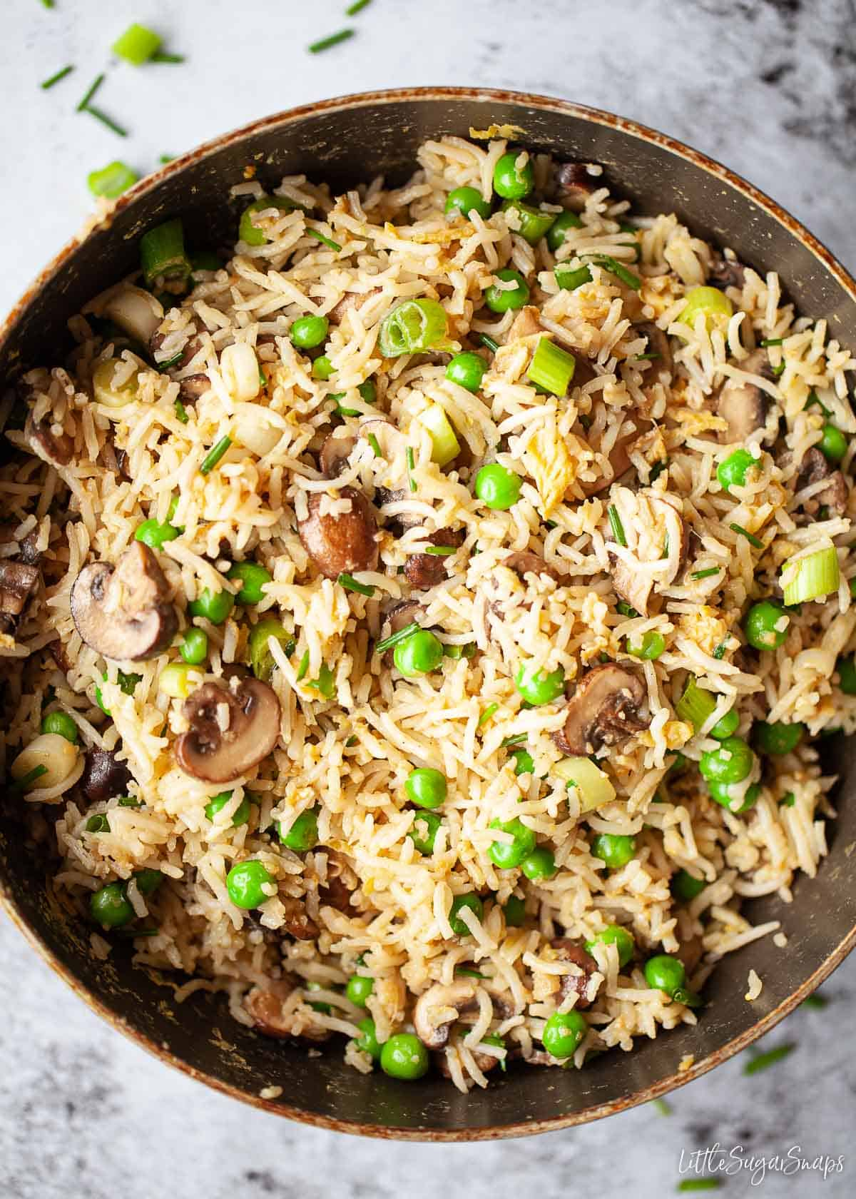 A pan of egg fried rice with mushrooms and peas