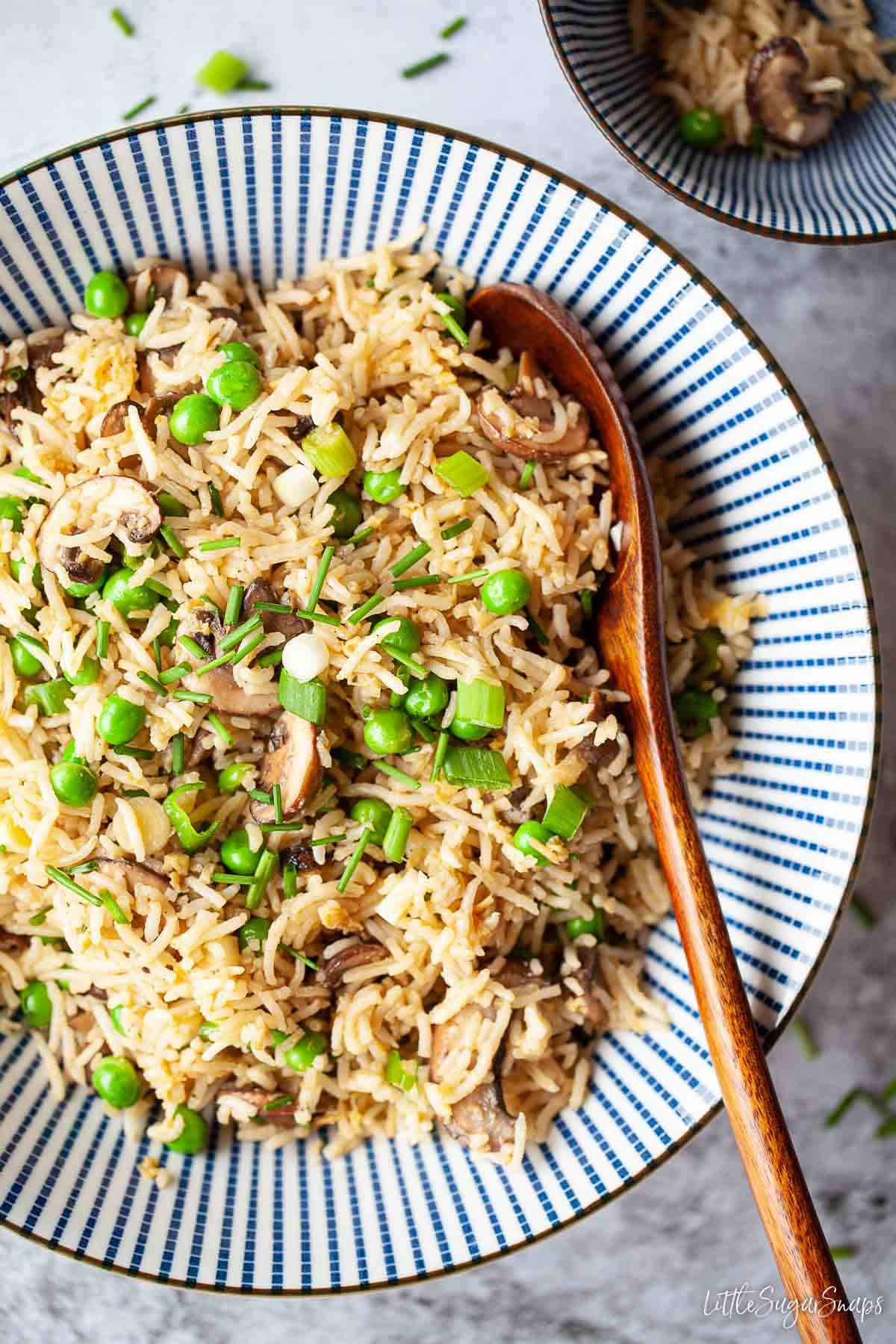 A bowl of fried rice with mushrooms with a serving spoon in it