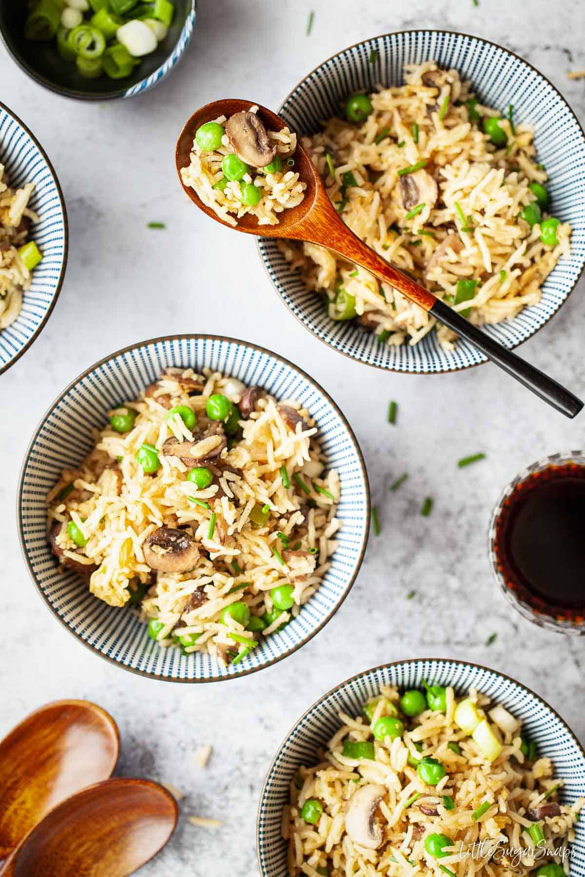 Three bowls of mushroom fried rice, one with a spoon across it.