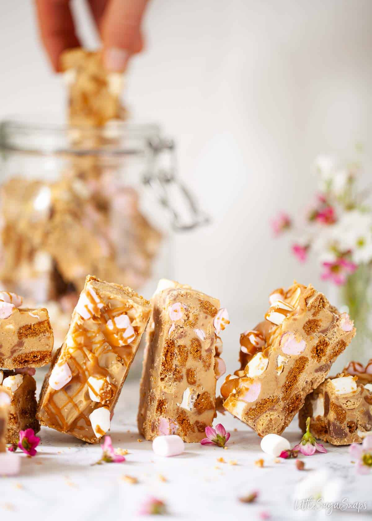 White chocolate and biscoff rocky road with a person taking a bar
