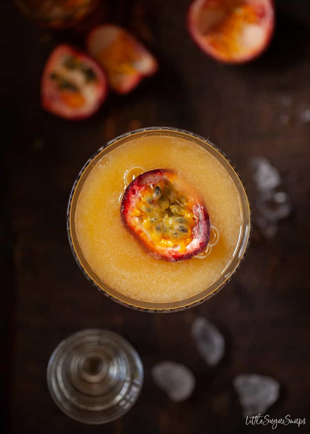 Overhead view of a passionfruit martini topped with fresh passionfruit