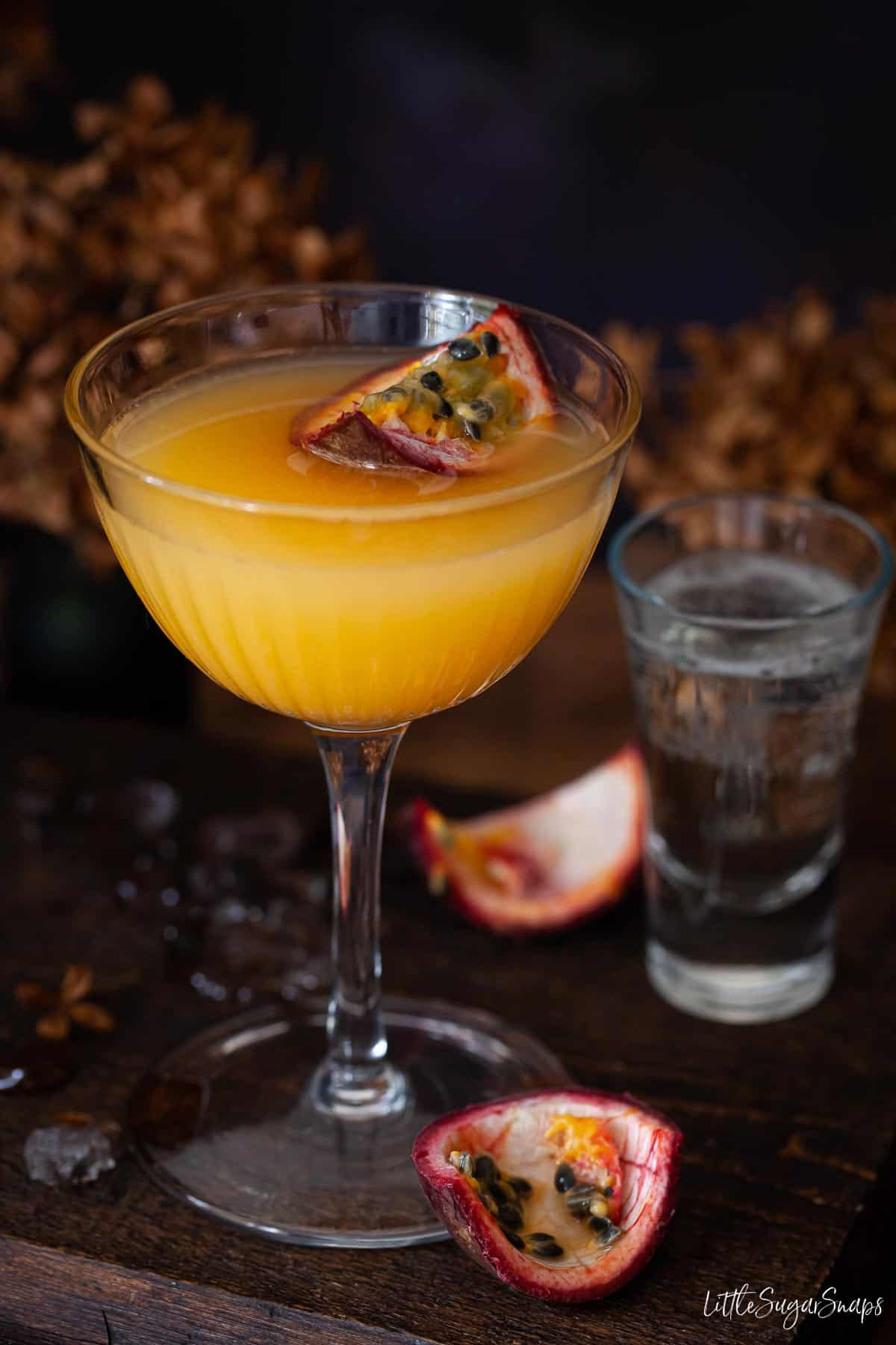 Passionfruit martini topped with fresh passionfruit and served with a glass of Prosecco