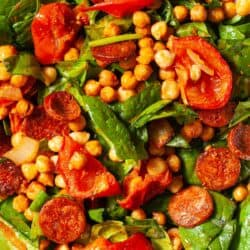 Close up of a roasted chickpea salad with spinach, tomato and chorizo