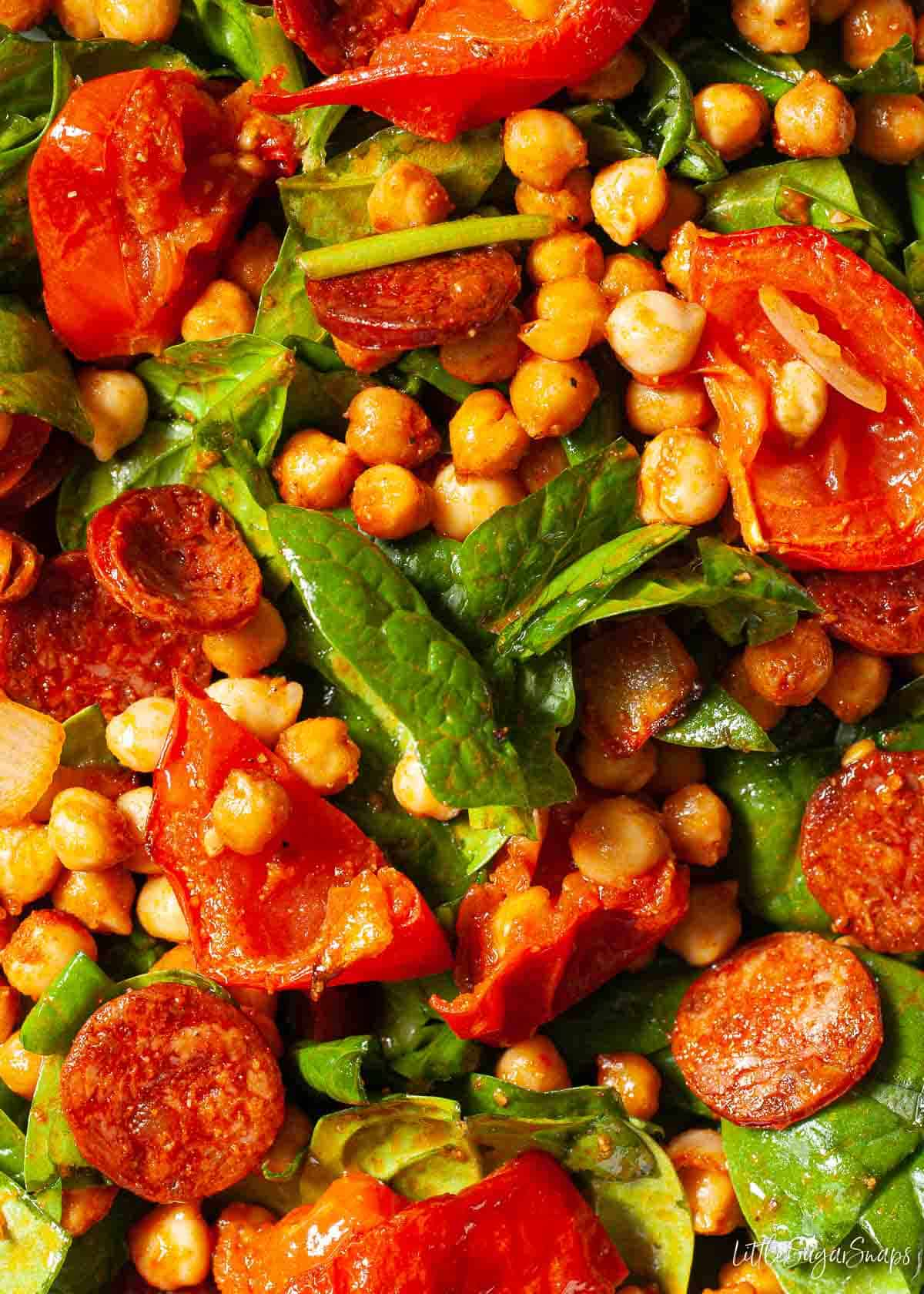 Close up view of roasted chickpea salad with spinach, tomatoes and chorizo
