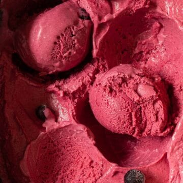 Close up of a tub of homemade blackcurrant ice cream with some scooped into balls