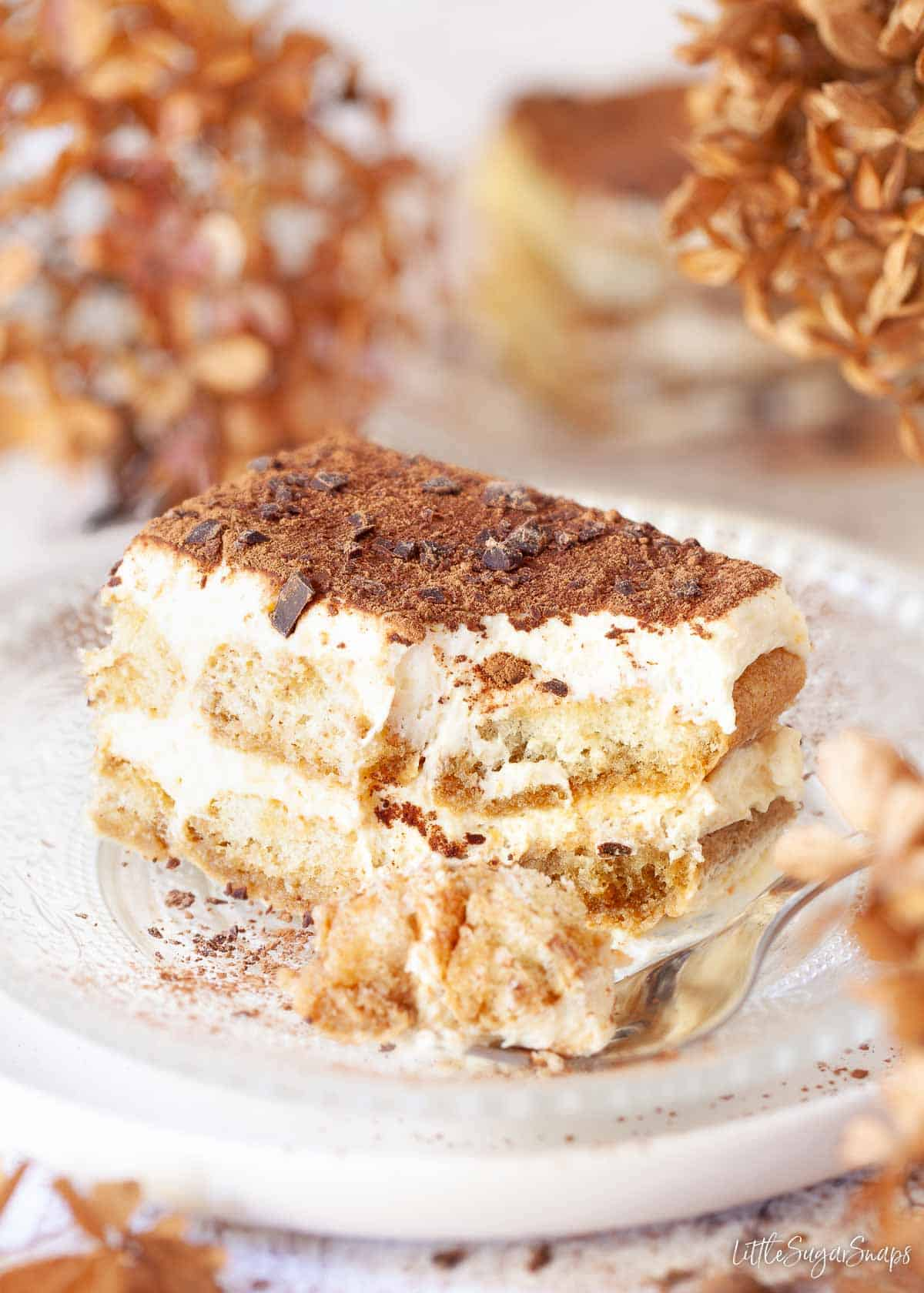 A piece of Italian tiramisu with a chunk taken out using a fork