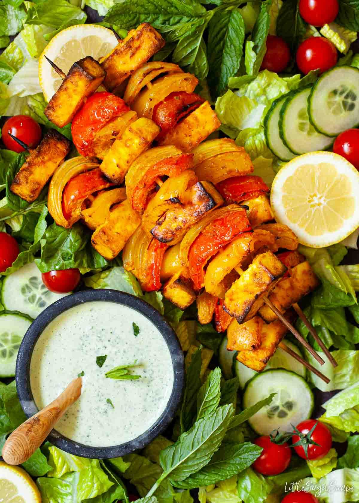 Paneer tikka kebabs presented on salad with spicy yoghurt sauce