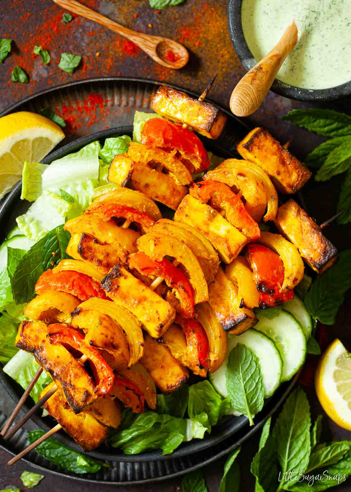 Paneer tikka on skewers with red and yellow peppers