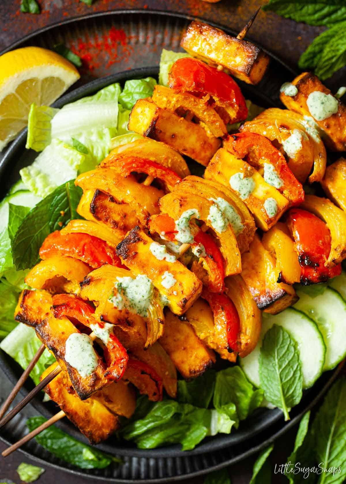 Paneer tikka kebabs on green salad with yoghurt sauce drizzled on top