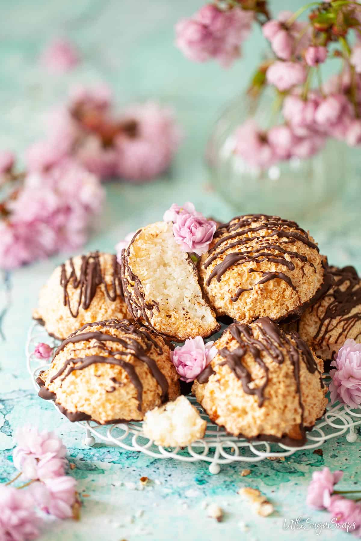 A plate of coconut macaroons with pink flowers surrounding it