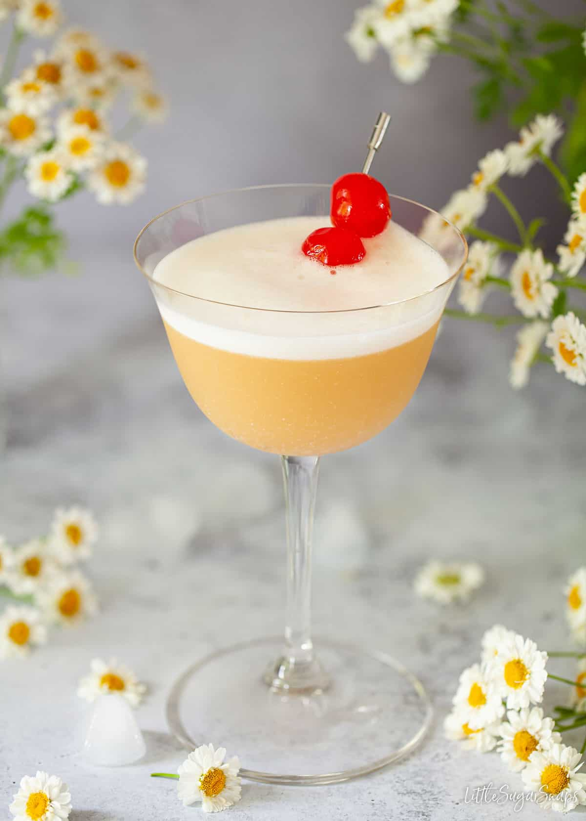 A Disaronno Amaretto sour cocktail garnished with egg white foam and cocktail cherries