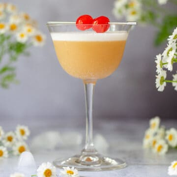 An Amaretto sour cocktail garnished with egg white foam and cocktail cherries