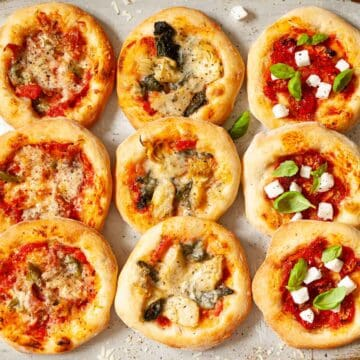 n assortment of pizzette - mini pizzas - on a baking sheet including meat pizza, vegetarian pizza and vegan pizza