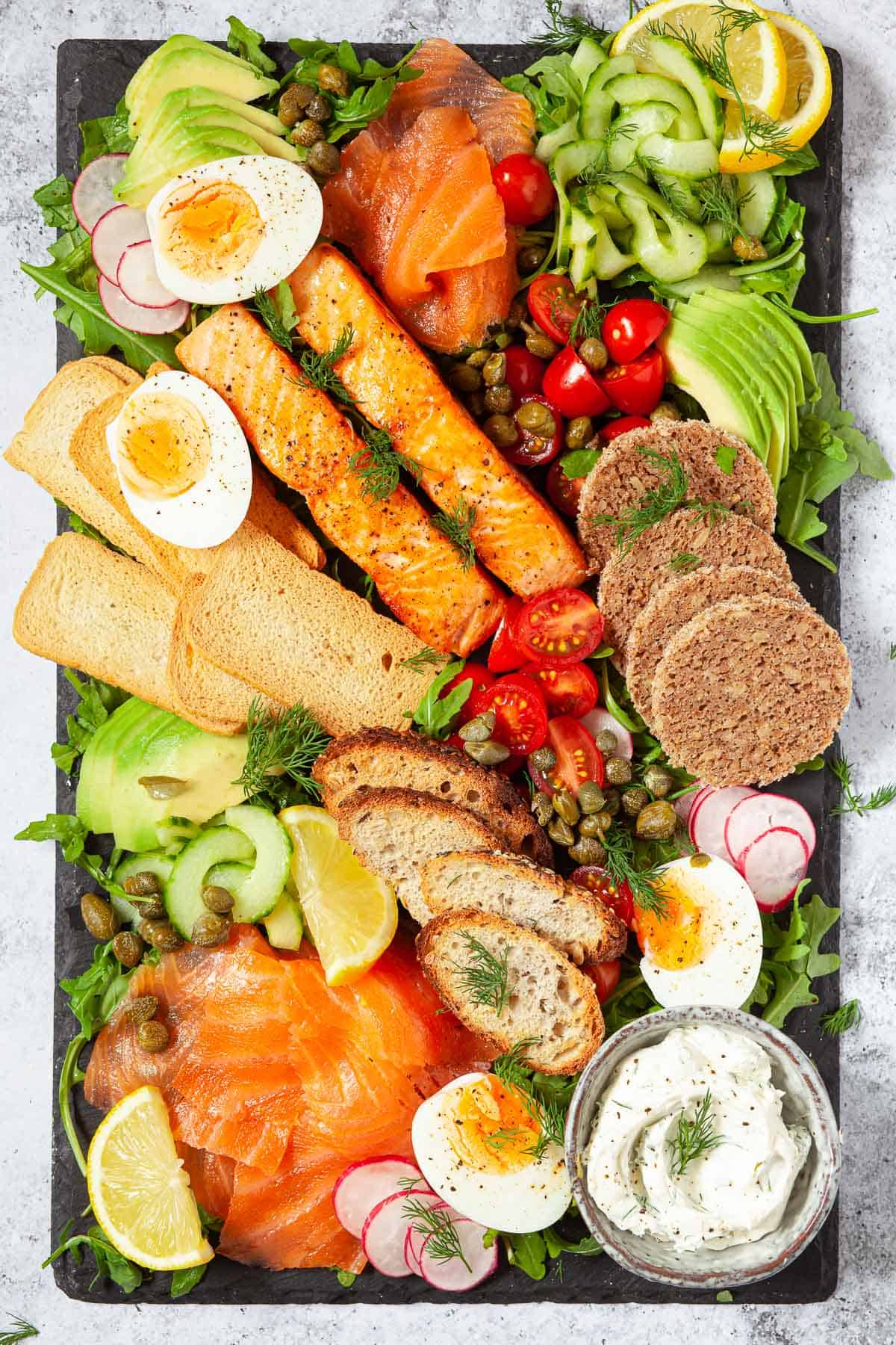 A salmon platter with eggs, vegetables and mixed toasts